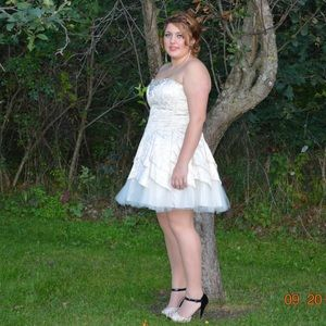 A cream colored homecoming dress with gold print.